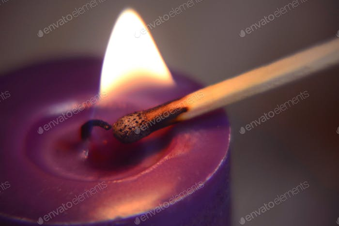 Close up of lighting a purple candle with matchstick