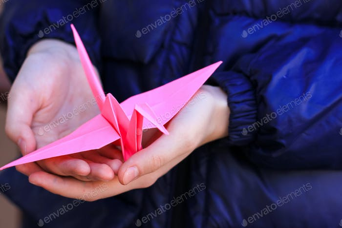 Bright origami paper crane in the hands of a teenage girl. hope, faith, happy future, peace symbol