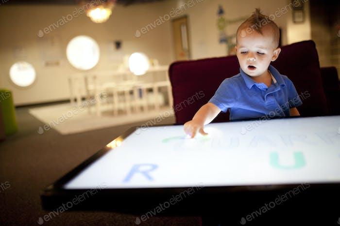 малыш играет на гигантском сенсорном экране устройства поверхности Microsoft