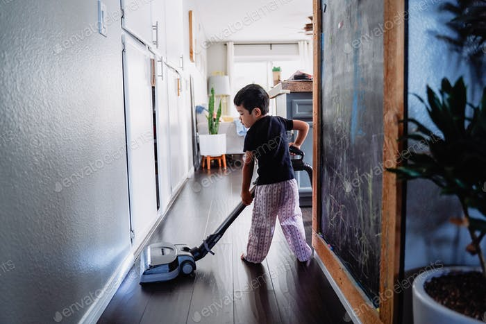 Diverse young little cute good boy house chores vacuum in pajamas.