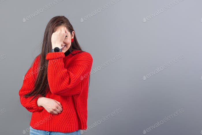 headshot of a happy emotional teenage girl with long hair dressed in a red sweater and jeans