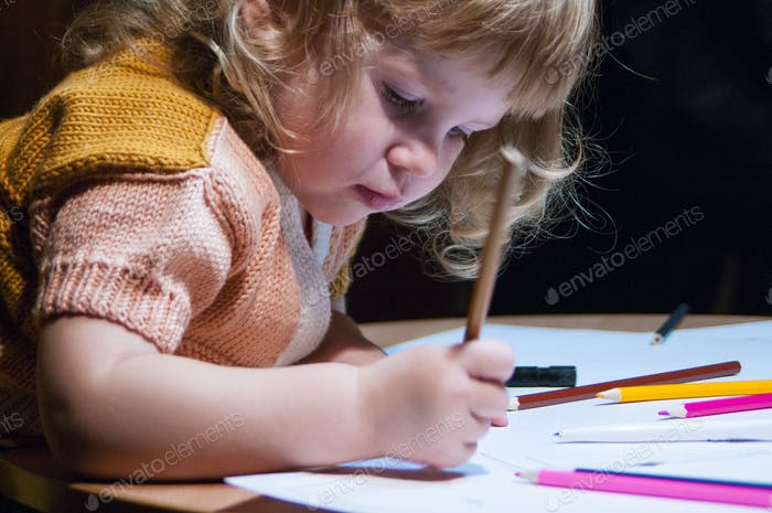 a child draws with colored pencils, kid, baby, child, toddler, babe, sitting at the table, classroom