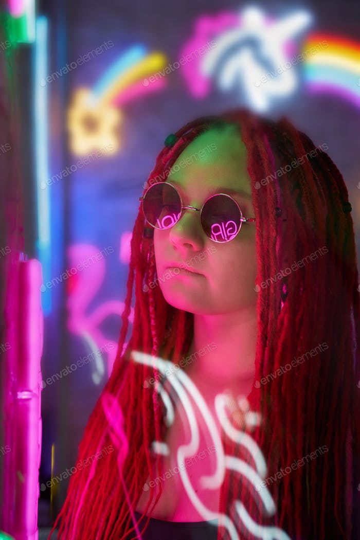 Girl in neon lights at party in nightclub, beautiful woman in sunglasses, with long pink hair, with
