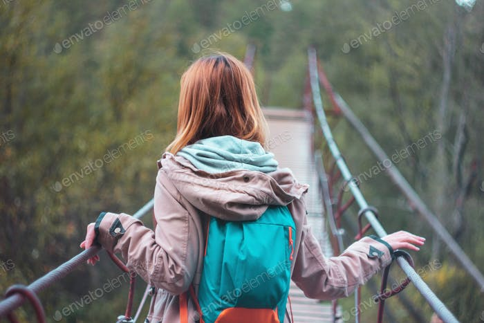 Girl traveler with red long hair on forest suspension bridge