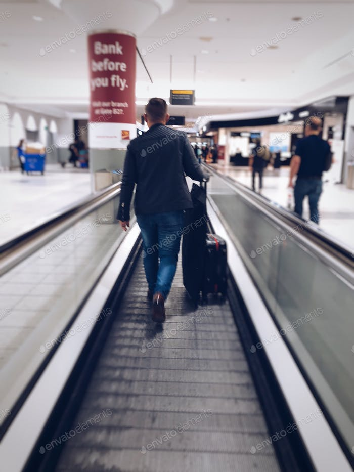 millennial man is walking on a moving floor with his carry on luggage and garment bag at the airport