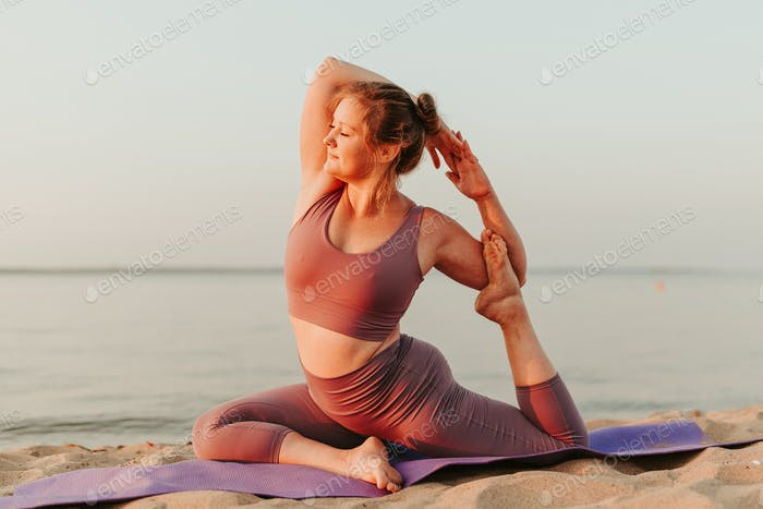 Young woman doing yoga on the sandy beach at summer sunrise. Body and mental health joy and pleasure