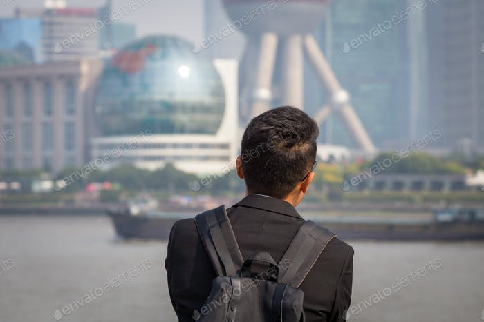 Asian man staring off at the Bund, Shanghai, China.