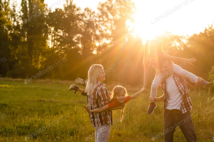 happy family with two children in the field at sunset