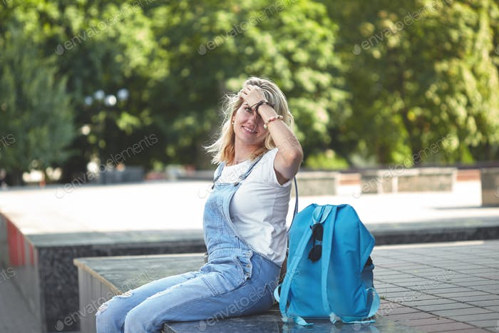 portrait of a young blonde girl in denim overalls sitting on the street