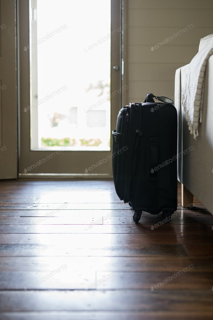 Black small weekend overnight travel bag near door waiting to leave