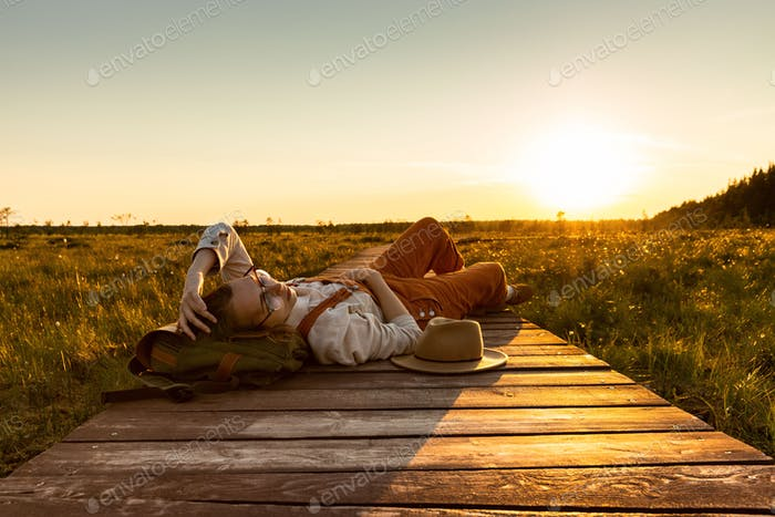 Woman naturalist lying on wooden path at sunset. Enjoys the moment of unity with nature.