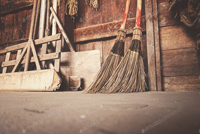 Old brooms placed against a wall with other cleaning stuff.