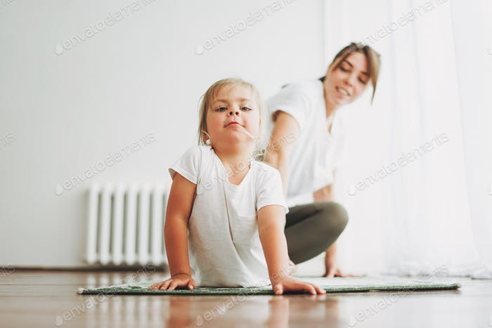 Mom and funny little daughter doing yoga morning exercise together at bright interior home