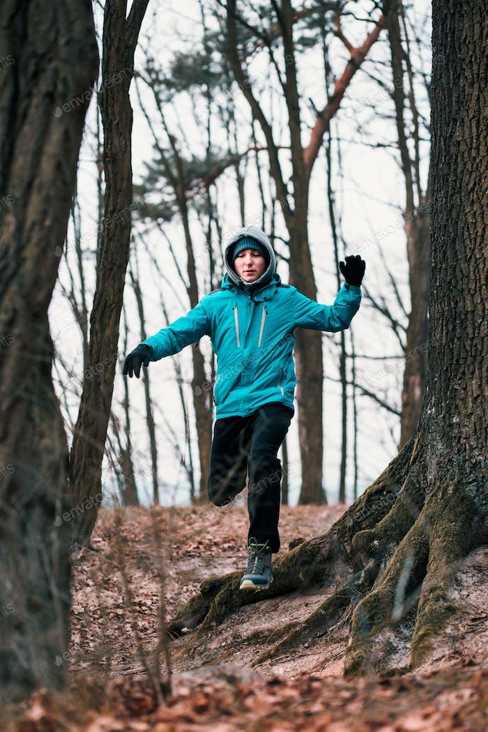 Молодой человек бежит на открытом воздухе во время тренировки в лесу среди безлиственных деревьев в холодный мороз осенний день