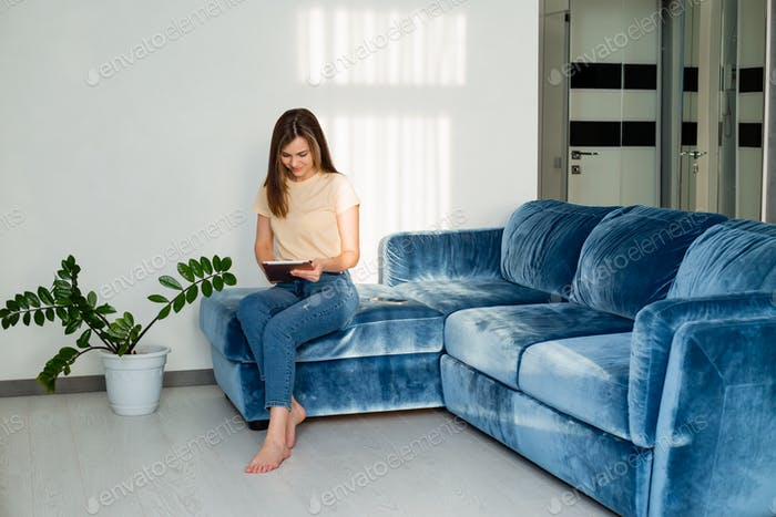 young girl sitting on the couch at home holding a tablet