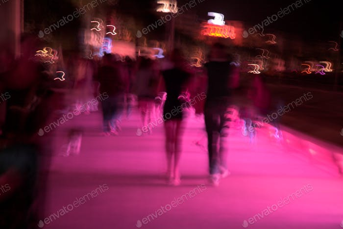 City nights, walking people in motion in a street at night, pink light, incidental people, urban