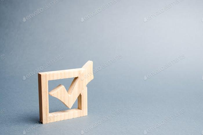 marca de verificación de madera para votar en las elecciones sobre un fondo gris