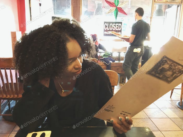 Young woman in restaurant looking at the menu and deciding what to order