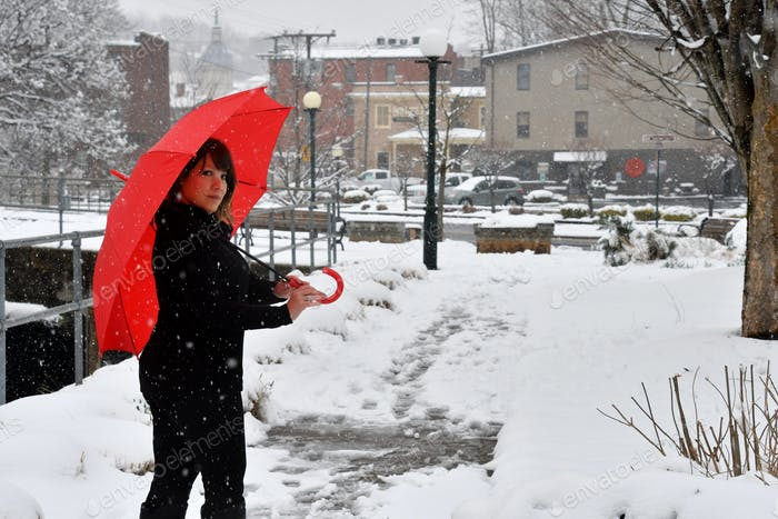 A Puerto Rican Latino woman with a lovely smile enjoying a snow day in the city with a red umbrella.