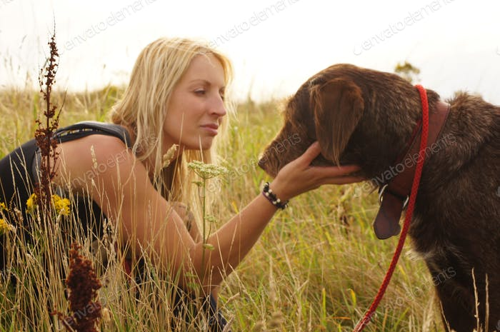 Blonde girl talking to her dog by holding his head in a loving way