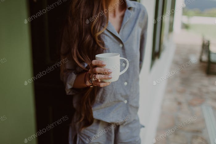 Woman drinking a cup of coffee.  Caffeine fix