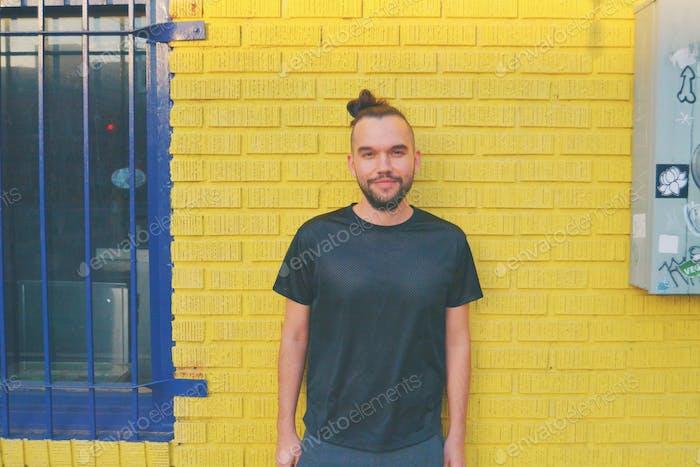 Latino hipster guy against yellow brick wall