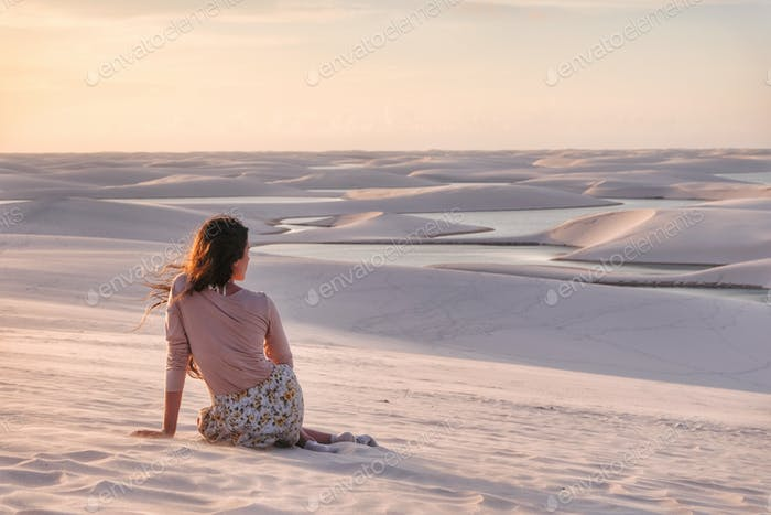 Girl sitting in the sand dunes watching the sunset at Lencois Maranhenses