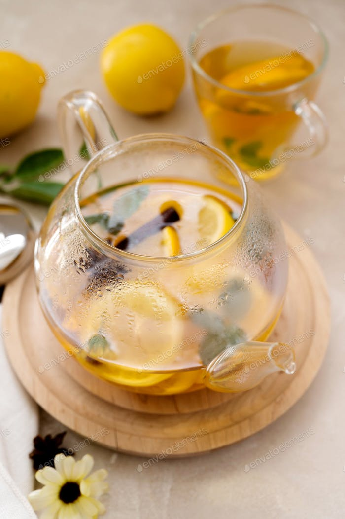 Glass teapot with fruit citrus tea on bright background. Herbal delicious healthy warm tea