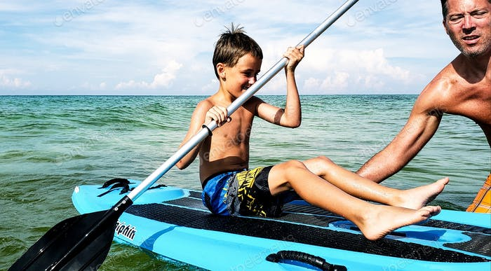 Little boy learning to paddleboard from his uncle who has never been a paddleboarder...