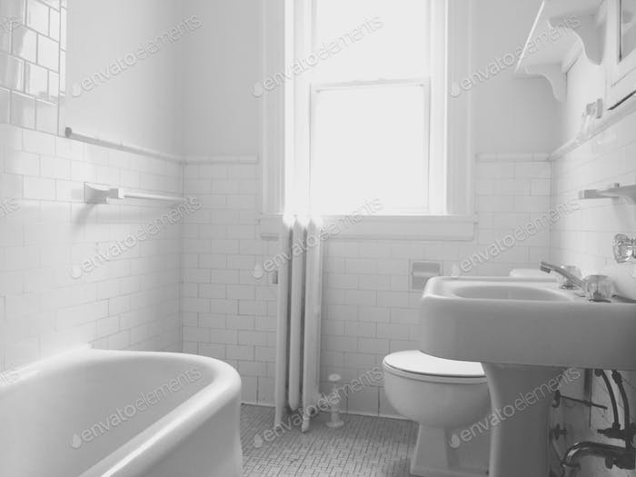 Desaturated black and white photo of a clean bathroom with white tiles