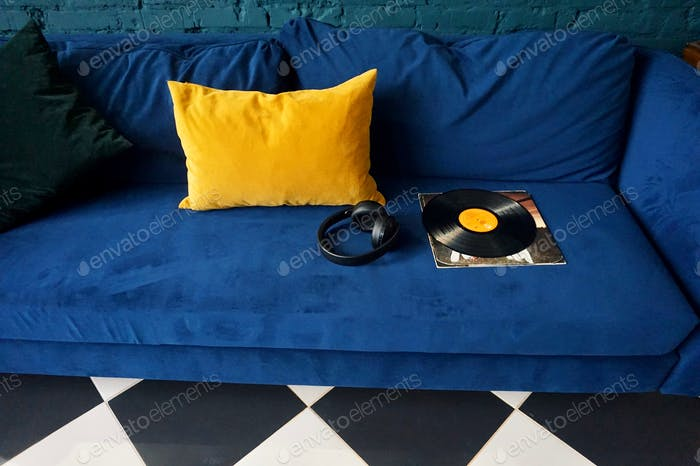 Vinyl record and headphones lying on the couch