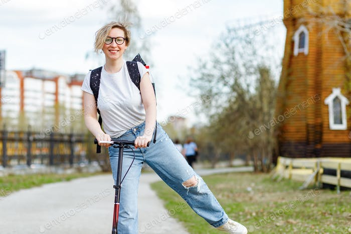young cheerful blonde girl rides a scooter in a city park