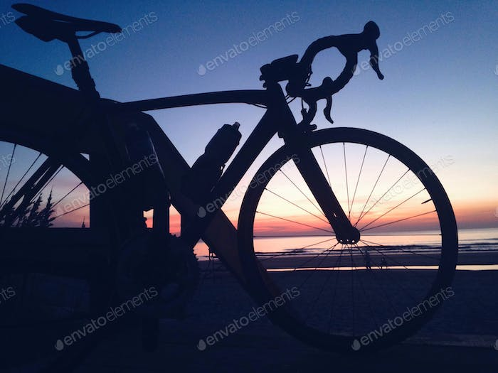 Silhouette of bicycle overlooking a beautiful ocean sunrise