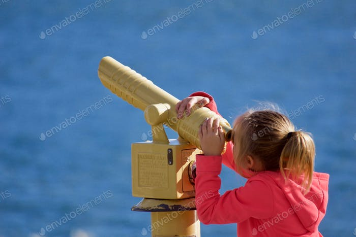 Young tourist girl using the viewfinder on her vacation to San Diego California