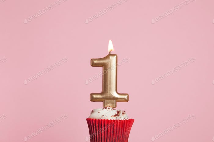 Gold number one birthday celebration candle in a cupcake