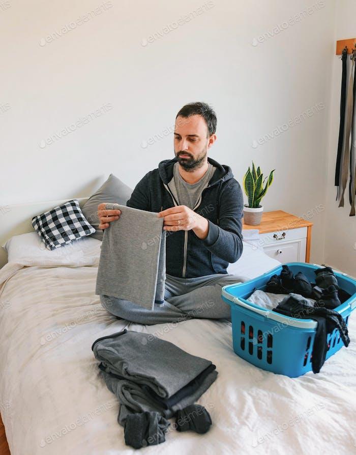 Junger Mann sitzt auf dem Bett und klappbare Wäsche. Hausarbeit, Haushalt, Mann, junger Mann, Mann tut lästige  Arbeit
