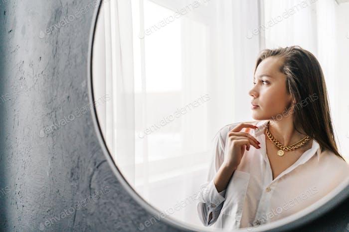 Silberne Bijouterie Kette mit Anhänger am Hals der Frau. Reflexionsfrau im Spiegel, Fensterhintergrund