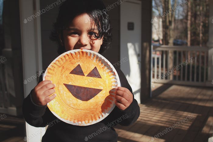 Happy kid holding handmade smiley card while sitting in sun and shadow