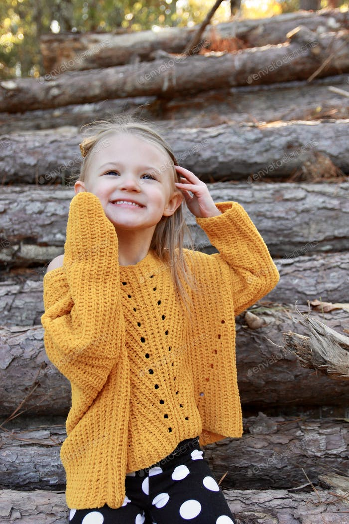 A little girl in fall clothes poses by a log pile in the woods.