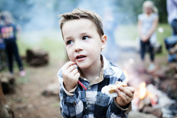 Boy eating a smore by a campfire while camping in the woods.