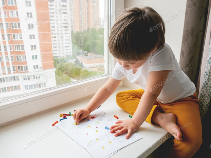 Toddler sits on windowsill and paints colorful fireworks