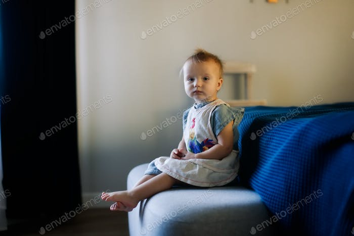 Sleepy toddler girl child in a dress near the bed in the bedroom, dark style