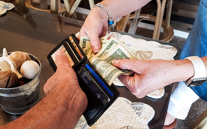Determined aggressive woman is removing money from a man