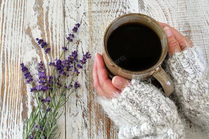 A woman in a cozy fuzzy sweater holding coffee mug in her hands on a distressed table with lavender
