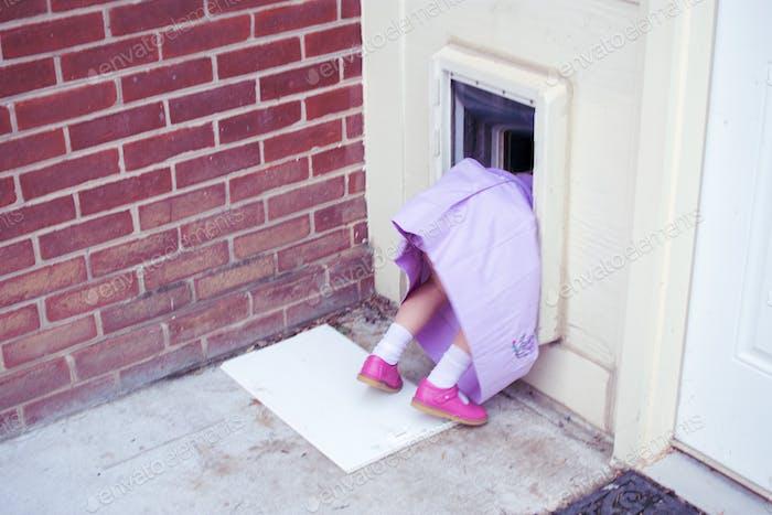 Niña en vestido púrpura y zapatos rosa tratando de entrar en la casa de una manera poco convencional