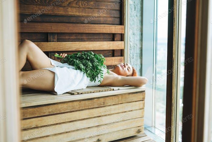 Woman in white towel lies on wooden shelf in Finnish sauna with rowan broom