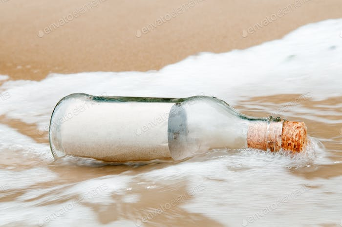 Close-up of glass bottle washed ashore on a beach.