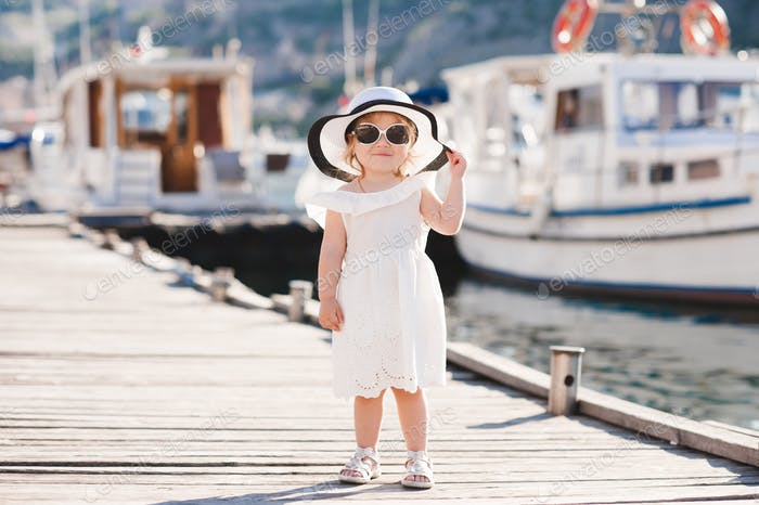 Smiling baby girl 1-2 year old wearing white summer dress and hat walking on wooden pier at sea
