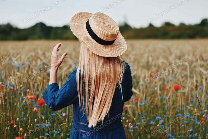 Rear view of blonde woman wearing straw hat in countryside