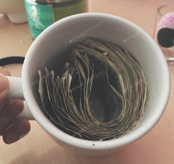 Blick von oben auf Tasse voller gefalteter Dollar-Scheine
